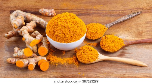 fresh turmeric roots with turmeric powder on wooden table
