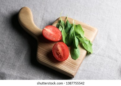 fresh two half cherry tomatoes with arugula herbs on a birch sma