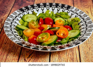 Fresh two-color cherry tomato salad, lettuce, red onion and hot chili served in a vintage bowl on a table.