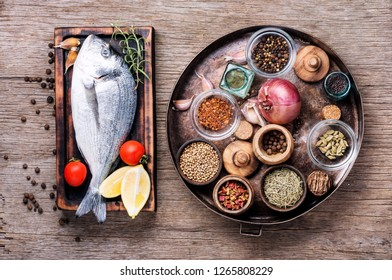 Fresh uncooked dorado fish with herbs and spices on rustic wooden board