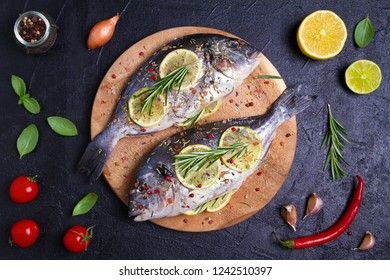 Fresh uncooked dorado or sea bream fish with lemon, herbs, vegetables and spices on black background. View from above, top