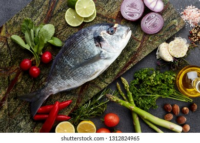 Fresh uncooked dorado and sea bream fish with lemon, rosemary, garlic, herbs, oil, vegetables and spices on rustic wooden board over black backdrop, top view, healthy food, diet or cooking concept,