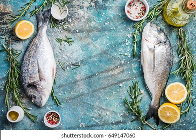 Fresh uncooked dorado or sea bream fish with lemon, herbs, olive oil and spices over blue background, top view with copy space