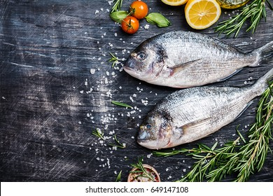 Fresh uncooked dorado or sea bream fish with lemon, herbs, olive oil and spices over black backdrop, top view with copy space