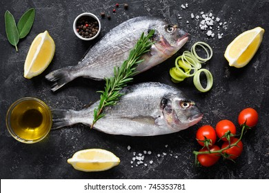 Fresh uncooked dorado or sea bream fish with lemon slices, spices, herbs and vegetables. Mediterranean cuisine. Top view