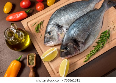 Fresh uncooked dorado or sea bream fish with lemon, herbs, oil, vegetables and spices on wooden board over dark backdrop, top view.