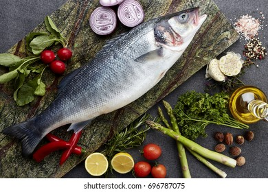 Fresh uncooked  sea bream fish with lemon, herbs, oil, vegetables and spices on rustic wooden board over black backdrop, top view
