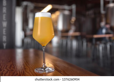 Fresh unfiltered craft beer IPA in stemmed glassware, on counter of microbrewery