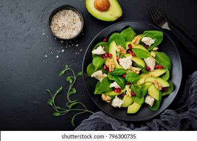 Fresh useful vegetarian wholesome avocado, spinach, pomegranate seeds, walnut, saffron, pepper and ricotta salad on  black background. Selective focus. Top view. Copy space for text.