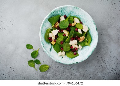 Fresh useful vegetarian wholesome spinach, pomegranate seeds, walnut, saffron, pepper and ricotta salad on  gray  background. Selective focus. Top view. Copy space for text.