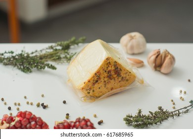 Fresh vacuum packed cheese with spices on a white table with garlic, pepper and herbs