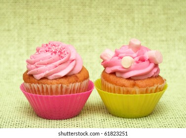 Fresh vanilla cupcakes in pink cup with strawberry icing on decorative background