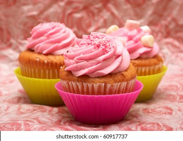 Fresh vanilla cupcakes in pink cups with strawberry icing and marshmallows on decorative background