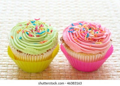 Fresh vanilla cupcakes with strawberry and lime icing on woven straw background