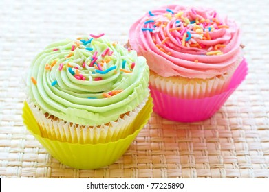 Fresh vanilla cupcakes with strawberry and lime icing on woven placemat background
