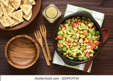 Fresh vegan chickpea, celery, grape and apple salad with parsley, homemade sesame pita chips and vinaigrette on the side, photographed overhead with natural light