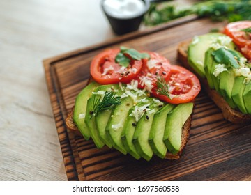 Fresh vegan homemade sandwich with avocado and tomatoes with dark grain bread on a wooden board. Close up