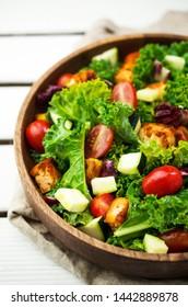 Fresh vegan salad, tofu, kale on wooden planks