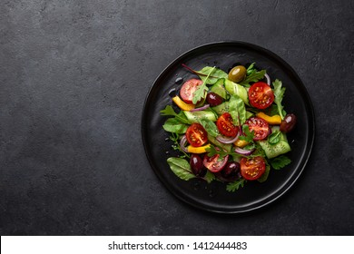 Fresh vegan salad with tomato, cucumber, bel pepper and olives salad on black plate, top view, dark background, copy space