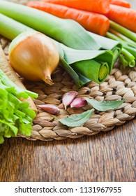 Fresh vegetable board - carrot, celery, leek, chili, onion, parsnip, parsley, bay leaf, garlic. Ingredients of broth, soup - cooking. European cuisine.