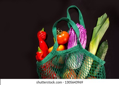 fresh vegetable, garden produce, clean eating and dieting concept. Vegetable in a net cotton bag on black background