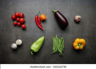Fresh vegetable ingredients on grey kitchen table
