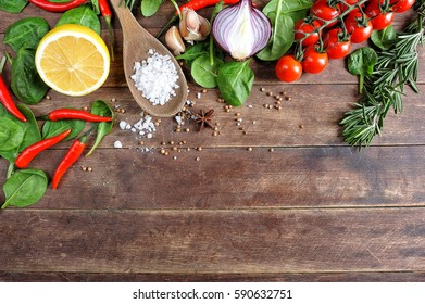 Fresh vegetable ingredients on vintage wooden background. Top view. Space for text