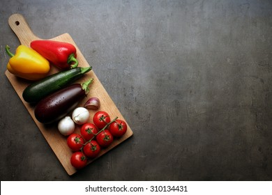 Fresh vegetable on wooden cutting board with space for your recipe text on grey kitchen countertop