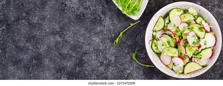 Fresh vegetable  radish and cucumber salad with green onions and microgreens peas on a dark background. Healthy food. Banner. Top view. Copy space.