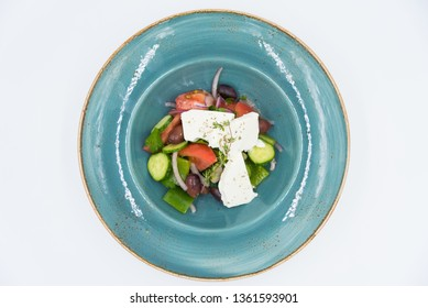 Fresh vegetable salad with cheese on the blue plate. Vegetarian food.
