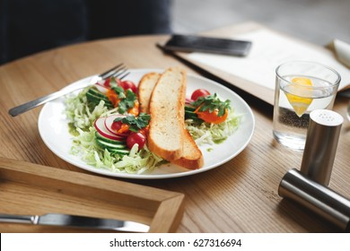 Fresh vegetable salad from cherry tomatoes, cucumbers, and cabbage with sea buckthorn sauce and toast bread