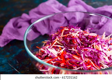Fresh vegetable salad coleslaw with red cabbage, white cabbage and carrot in glass bowl on vintage background. Healthy eating.