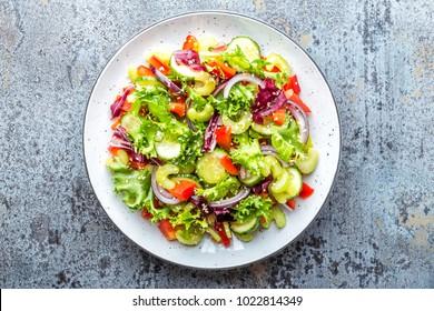 Fresh vegetable Salad of cucumber, celery, sweet pepper, frize lettuce, red onion and sesame seeds with olive oil. Healthy vegetarian, vegan food