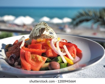 Fresh vegetable salad with feta cheese on white plate. Food on the beach.