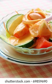 Fresh vegetable salad in glass bowl topped with thousand island dressing