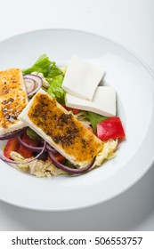 Fresh vegetable salad with grilled cheese on white background