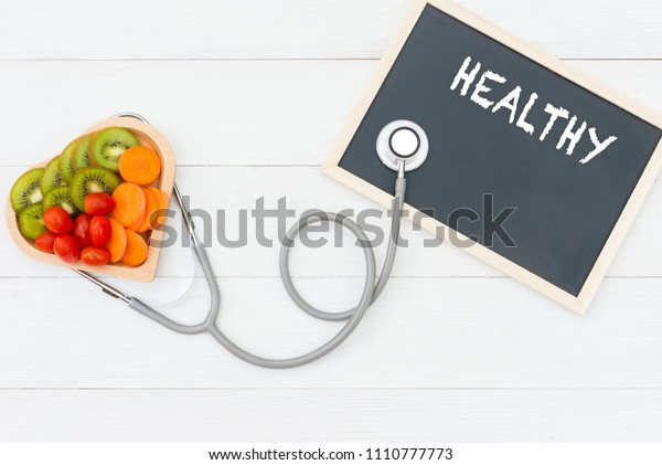 Fresh vegetable salad and healthy food on the shape heart with medical stethoscope for diet and weight loss on the old white wooden.  Healthy Concept.