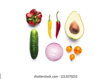 Fresh vegetable salad ingredients: avocado, cucumber, paprika, onion, tomatoes and chilli peppers on white background, top view