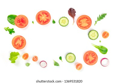 Fresh vegetable salad ingredients, shot from above on a white background. A flat lay composition with tomato, cucumber, onion slices and mezclun leaves, forming a frame with a place for text
