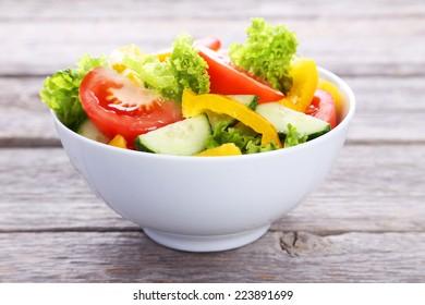 Fresh vegetable salad on grey wooden background