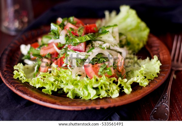 Fresh vegetable salad on the plate, close up rustic photo