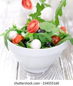 Fresh vegetable salad over wooden background