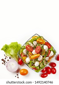 Fresh vegetable salad; sliced cucumber, red and yellow tomatoes, mozzarella cheese, caprese; onion slice, lettuce leaves and pistaches on white background. Top view. Place for text.