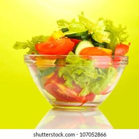 fresh vegetable salad in transparent bowl on green background