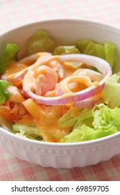 Fresh vegetable salad in white bowl topped with thousand island dressing