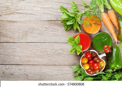 Fresh vegetable smoothie on wooden table. Tomato, cucumber, carrot. Top view with copy space