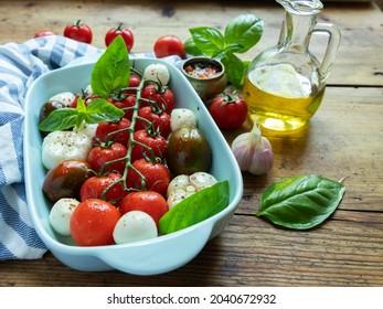 Tomate de légumes frais, basilic, fromage mozzarella à cuire dans le four en céramique. cuisson