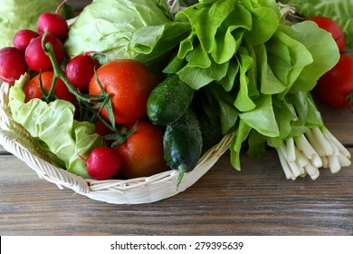 Fresh vegetables in a basket (cucumber, tomatoes, cabbage, greens)