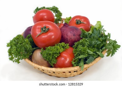Fresh vegetables in a basket on a white background.