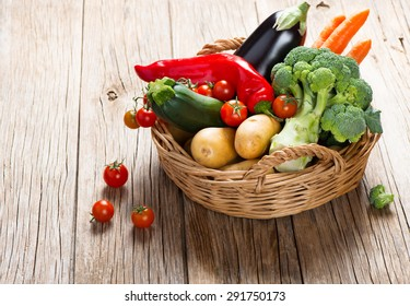 Fresh vegetables ( carrot, broccoli, potato, tomato, zucchini, eggplant and  bell pepper) in a basket  on a rustic wooden table
